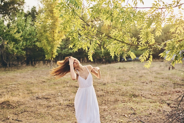 Mulher em um campo perto de uma árvore em uma floresta