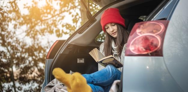 Mulher em um carro com meias quentes de lã amarela está lendo um livro enquanto está sentada no porta-malas de um carro em um piquenique