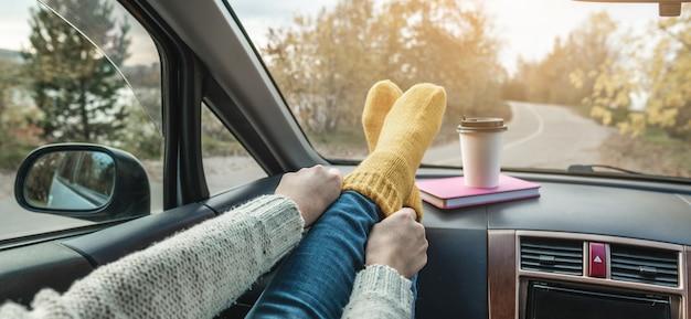Mulher em um carro com meias quentes de lã amarela no painel do carro