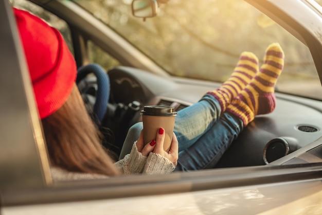 Mulher em um carro com meias quentes de lã amarela segurando uma xícara de café nas mãos ao pôr do sol
