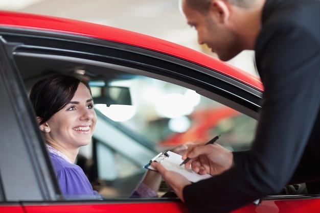 Mulher em um carro conversando com um vendedor