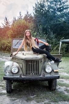 Mulher em um carro militar posando ao ar livre