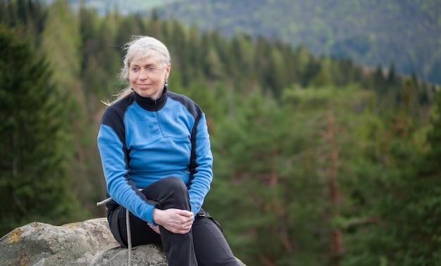 Mulher, em, um, casaco azul, sentar, e, relaxe, ligado, a, pico, de, rocha