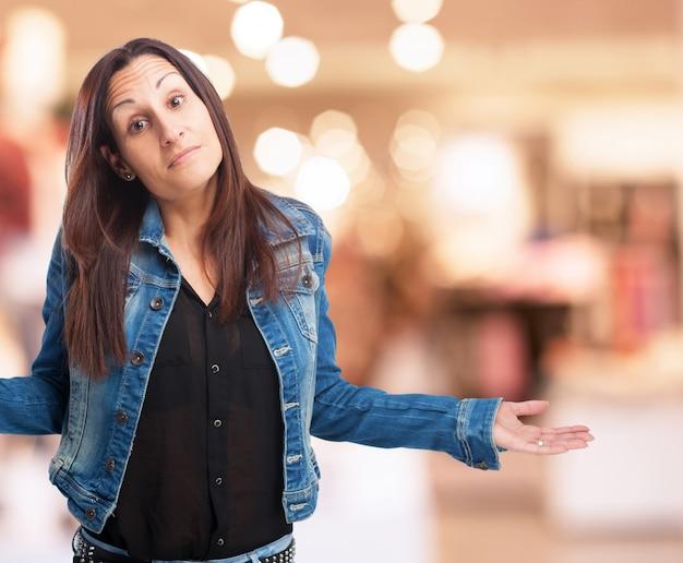 Mulher em um casaco de ganga com os ombros e as palmas das mãos levantadas