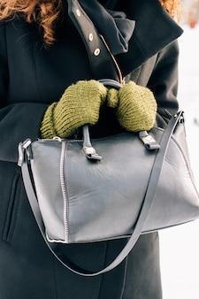 Mulher em um casaco preto e luvas verdes