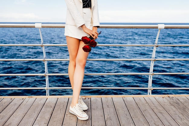 Mulher em um elegante terno branco minimalista e óculos de sol redondos retrô, segurando pequenas rosas vermelhas