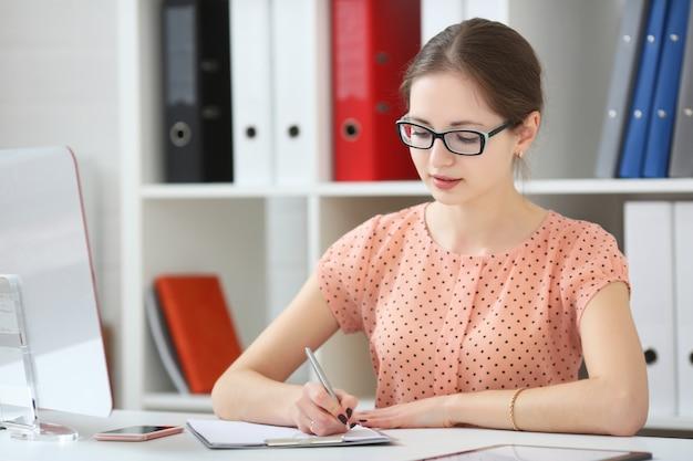 Mulher em um escritório toma notas em um diário
