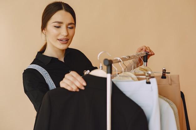Mulher em um estúdio com muitas roupas