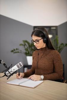 Mulher em um estúdio de rádio com fones de ouvido e microfone