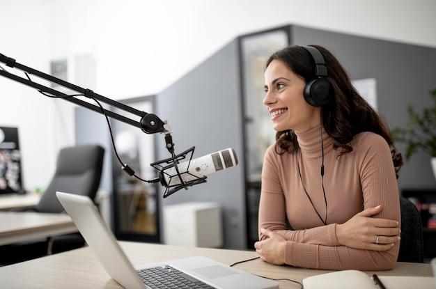 Mulher em um estúdio de rádio com microfone e laptop