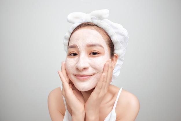 Mulher em um fundo branco, creme facial limpo na toalha facial no cabelo na cabeça