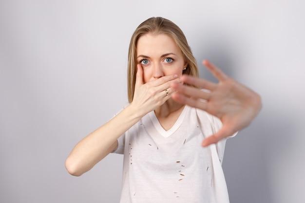 Mulher em um fundo branco fecha a boca com a mão contra a violência
