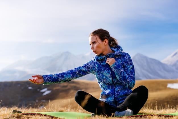 Mulher em um fundo de altas montanhas praticando ioga
