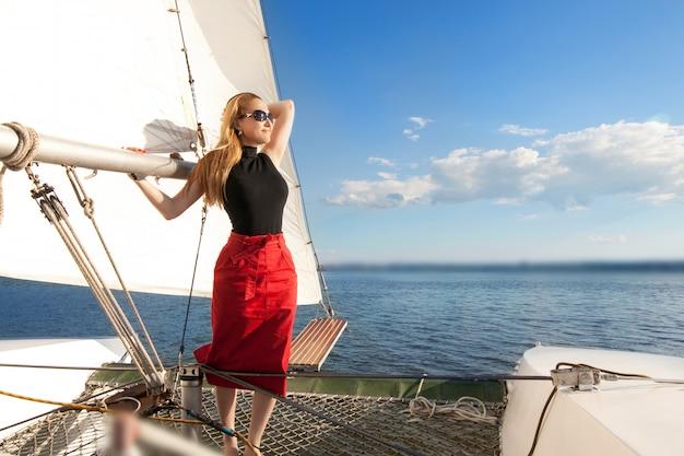 Mulher em um iate, contra as velas do céu e do mar. o conceito de iatismo e umas férias à beira-mar.