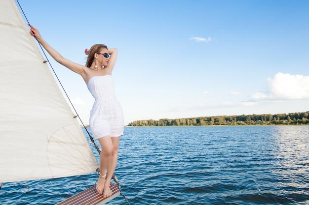 Mulher em um iate contra o espaço do mar branco e velas
