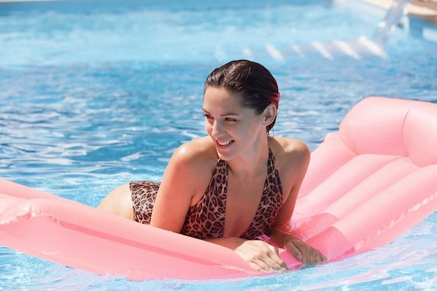 Mulher em um inflável rosa na piscina usando maiô com estampa de oncinha, sorrindo à parte