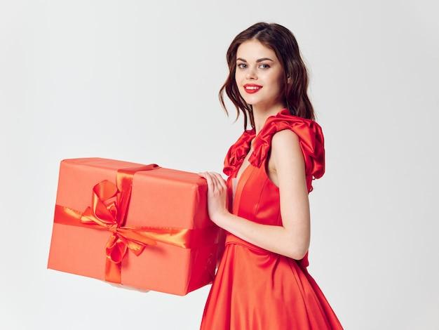 Mulher em um lindo vestido com caixas de presente de feriado no estúdio, venda e celebração