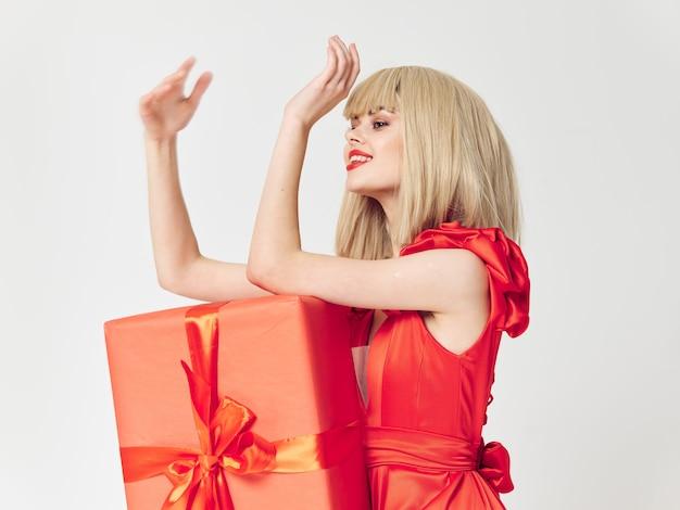 Mulher em um lindo vestido com caixas de presente de feriado, venda e celebração