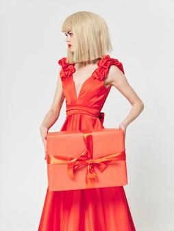 Mulher em um lindo vestido com caixas de presente no estúdio, venda e celebração