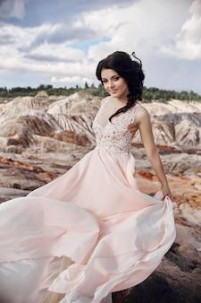 Mulher em um lindo vestido rosa nas montanhas fabulosas. o vestido longo esvoaçava ao vento. bela morena sozinha com a natureza. cuidados com a pele, pele linda