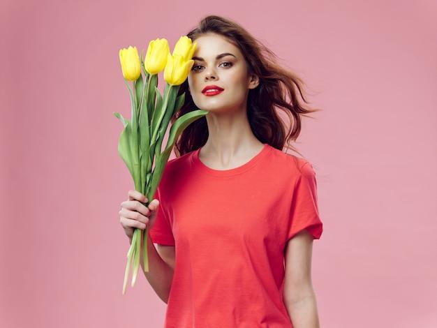 Mulher em um lindo vestido vermelho com uma rosa e pétalas de rosa