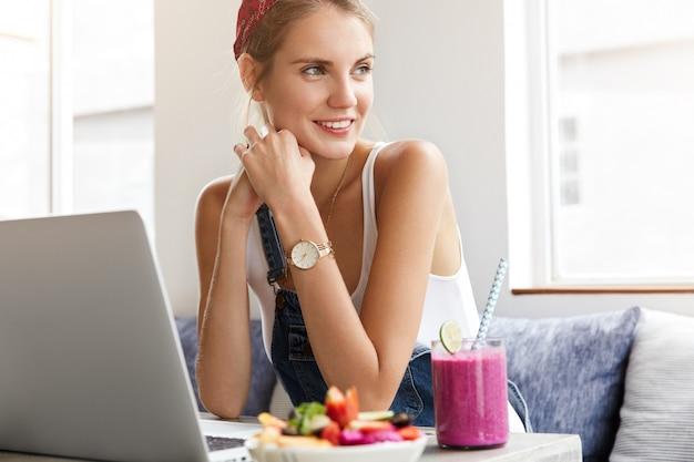 Mulher em um macacão jeans elegante com laptop na cafeteria