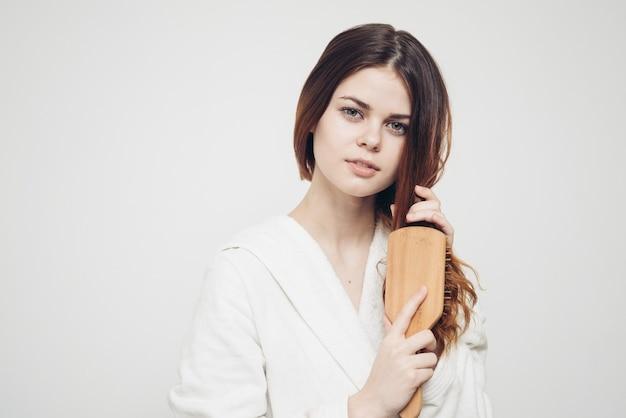 Mulher em um manto branco com um pente de madeira e modelo de cabelo comprido.