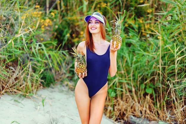Mulher em um monokini na costa do mar de uma ilha tropical