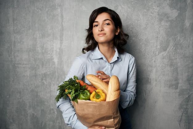 Mulher em um pacote de camisa azul com entrega de produtos hortícolas de supermercado