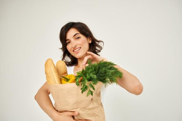 Mulher em um pacote de camiseta branca com entrega de comida saudável de supermercado