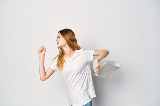 Mulher em um pacote de camiseta branca nas mãos, comprando um presente de fundo claro