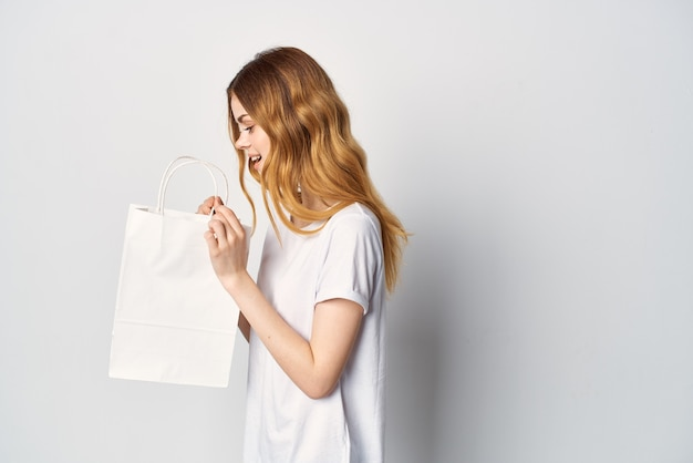 Mulher em um pacote de camiseta em mãos comprando na loja