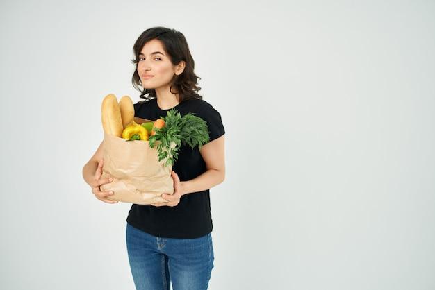 Mulher em um pacote de camiseta preta com compras de supermercado de mercearia