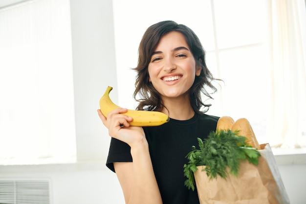 Mulher em um pacote de camiseta preta com produtos vegetais frutas alimentos saudáveis