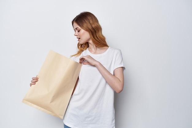 Mulher em um pacote de t-shirt branca com fundo claro de compras de mantimentos. foto de alta qualidade