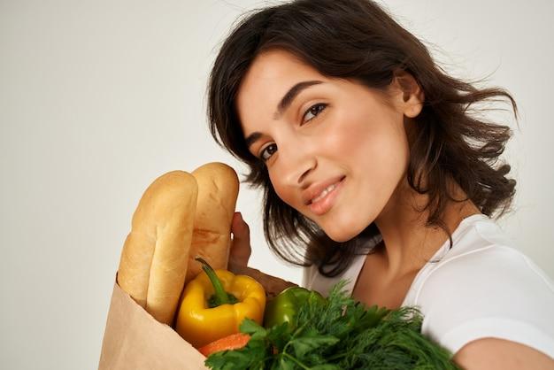 Mulher em um pacote de t-shirt branca com mercearia close-up de um supermercado. foto de alta qualidade