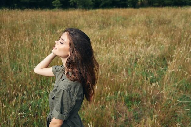 Mulher em um prado curtindo a natureza, olhos fechados, sol, ar fresco