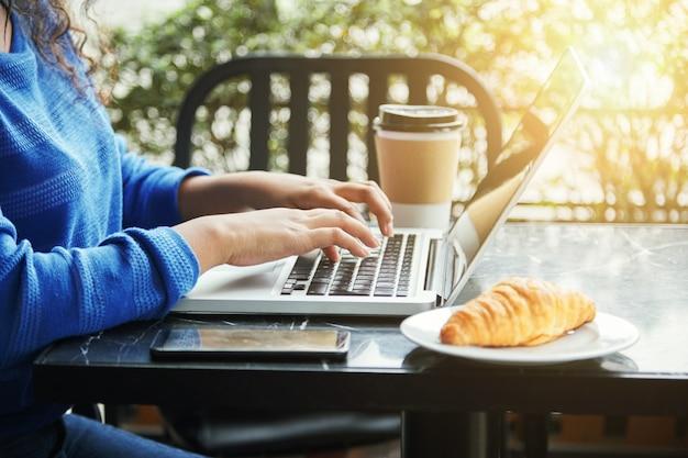 Mulher em um restaurante com sua xícara de café e laptop