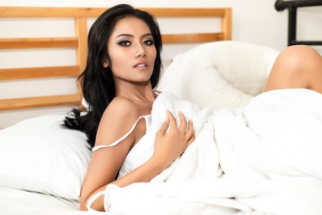 Mulher em um roupão branco transparente reclinado na cama de manhã.