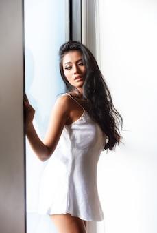 Mulher em um roupão branco transparente sentado olhando pela janela de manhã.