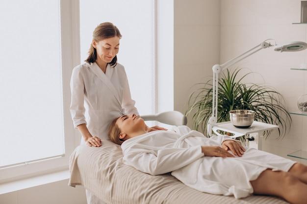 Mulher em um salão de beleza fazendo massagem no rosto e pescoço