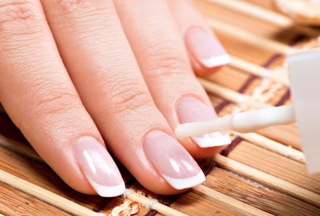 Mulher em um salão de beleza recebendo manicure por uma esteticista. conceito de tratamento de beleza.