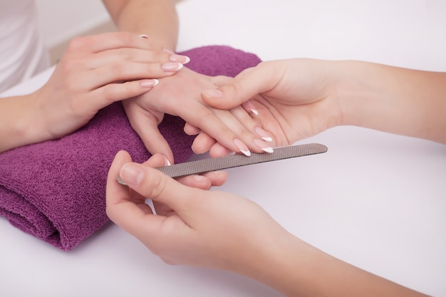 Mulher em um salão de beleza recebendo uma manicure por uma esteticista