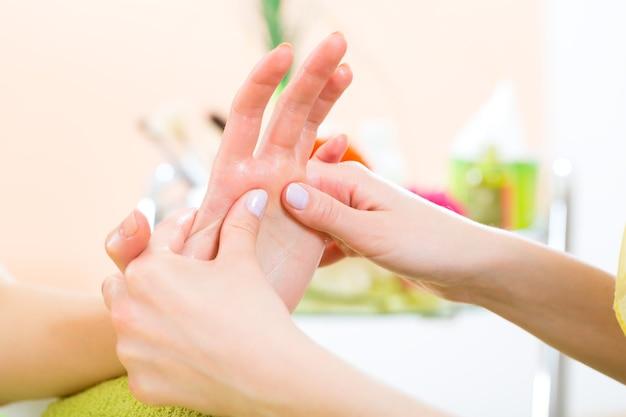 Mulher em um salão de manicure recebendo uma manicure de uma esteticista, ela está recebendo uma massagem nas mãos