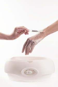 Mulher em um salão de manicure recebendo uma manicure, ela está lavando as mãos com parafina ou cera