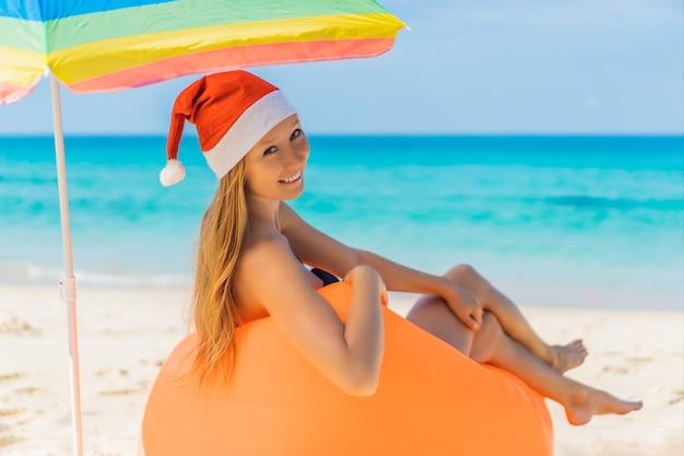 Mulher em um sofá inflável na praia sob um guarda-chuva