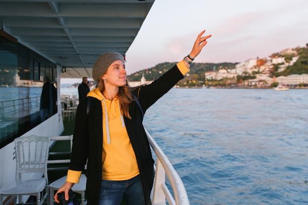 Mulher em um suéter amarelo e boina cinza em pé no convés do navio de cruzeiro