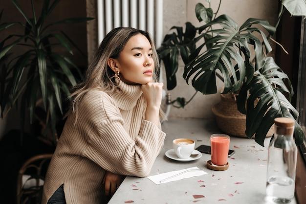 Mulher em um suéter bege elegante parece pensativa ao longe, apoiada na mesa com uma xícara de café e suco fresco