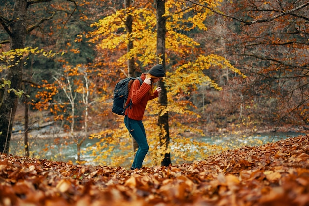 Mulher em um suéter jeans e com um chapéu na cabeça paisagem folhas caídas modelo