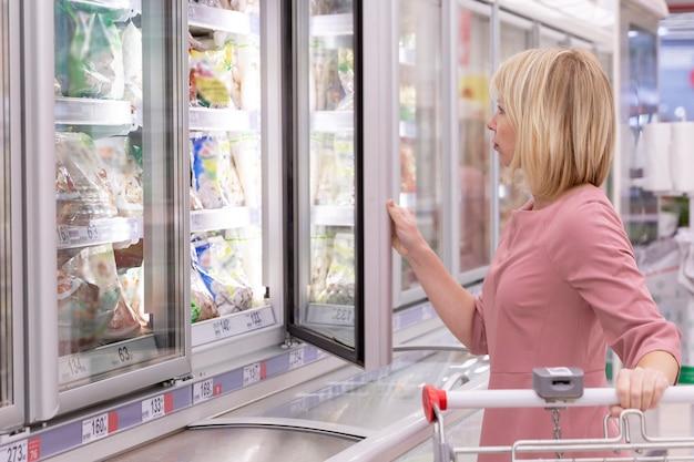 Mulher em um supermercado escolhe alimentos congelados em vitrines refrigeradas. loira adulta.